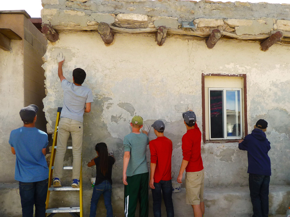 Participants plastering buildings in Hopi Pueblo