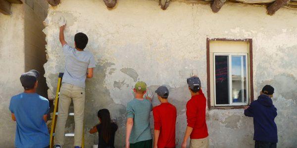Participants plastering buildings in Hopi Pueblo